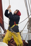 Young sailor at work. Young sailor on a ship's deck hoisting a sail royalty free stock image