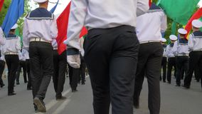 Young sailors in white uniform on parade marching with multicolored flags in the street stock footage