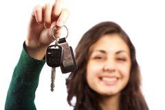 Young sales lady offering car keys. Young saleswoman handing over car keys, isolated on white background Stock Image