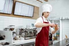 Salesman making ice cream at the pastry shop. Young salesman in apron and hat making ice cream with waffle cone at the modern pastry shop stock photography