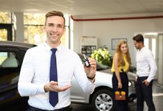 Young salesman with car key. In dealership royalty free stock image