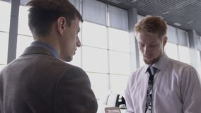 Young salesman and client is communicating, standing in modern auto salon, discussing transaction on background of car. Showroom and working people. slow motion stock video footage
