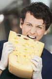 Young Salesman Eating Cheese In Store. Portrait of young salesman eating cheese in store royalty free stock photos