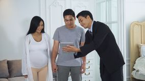 Salesman advising the customer on the furniture with tablet. Young salesman invite the furniture to the spouse with information in tablet at showroom example stock photo