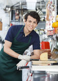 Young Salesman Leaning On Counter In Cheese Shop. Portrait of happy young salesman leaning on counter in cheese shop Royalty Free Stock Image