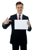 Young salesman pointing towards blank billboard Stock Photo