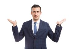 Young salesman or real estate agent presenting two options with. Hands looking like scales or balance on white isolated background royalty free stock image