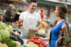 Young salesman smiling and holding vegetable at market stock photo
