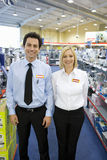 Young salesman and woman in electronics aisle, smiling, porttrait Stock Images