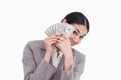 Young saleswoman covering her face with bank notes Royalty Free Stock Image