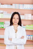 Young saleswoman with folded arms in a drug store Royalty Free Stock Photos