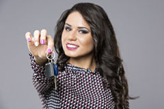 Young saleswoman handing over car keys. Isolated on gray background Royalty Free Stock Photography