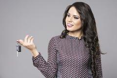 Young saleswoman handing over car keys Stock Image