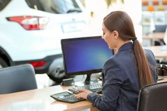 Young saleswoman sitting at table in car. Salon royalty free stock photos