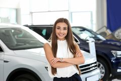 Young saleswoman standing in modern car. Salon royalty free stock image