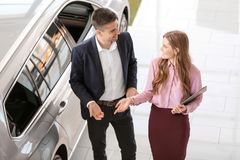 Young saleswoman working with client. In car dealership stock photos