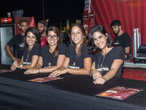 Young saleswomen happily posing near the counter at the traditional annual beer festival in Haifa, Israel. Haifa, Israel, August 16, 2017 : Young saleswomen Royalty Free Stock Photos