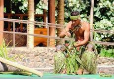 A young Samoan man demonstrating the art of weaving. Honolulu, Hawaii - May 27, 2016: A young Samoan man demonstrating the art of weaving in the Village of Samoa royalty free stock photography