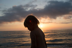 Young sand dirty child girl silhouette looking away beach shore. Warm sunset light. Family summer travel vacations at Royalty Free Stock Photo