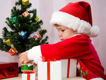 Young Santa. The small child in a suit of Santa Claus puts gifts under a fur-tree Stock Photography