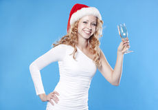 Young Santa girl drinking a champagne Royalty Free Stock Image