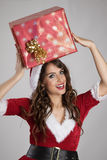 Young Santa helper girl carrying big present package on her head Royalty Free Stock Photography