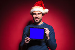 Young santa man holding a blue screen tablet pad computer. Young santa man holding a tablet pad computer with a blue screen, smiling for the camera royalty free stock images