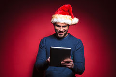 Young santa man smiling while reading tablet computer Stock Image