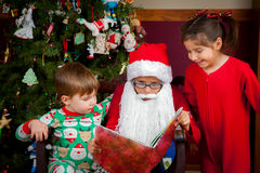 Young Santa Reads to Kids. A young girl with a Santa hat reads to a little girl and boy in front of a decorated Christmas tree Stock Photo