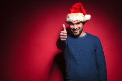 Young santa showing thumbs up sign. Sexy young santa showing thumbs up sign, smiling for the camera. On red background Stock Images
