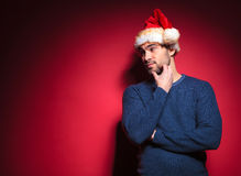 Young santa thinking while scratching his beard Stock Photos