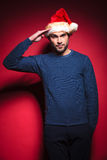 Young santa wearing a blue sweater saluting Royalty Free Stock Photography