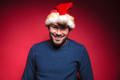 Young santa wearing a blue sweater smiling for the camera Stock Images