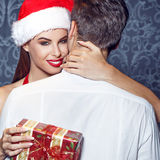Young santa woman embrace man by neck Stock Photos