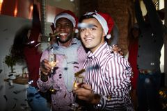 Young Santas. Intercultural guys with champagne and their friends enjoying dances on background Stock Photo