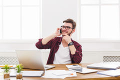 Young satisfied businessman has a mobile talk in modern white office. Young businessman in casual has mobile phone talk in modern white office interior Royalty Free Stock Photography