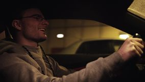 Young satisfied guy driving car in underground tunnel. Young satisfied caucasian unshaved guy in glasses and gray hoodie driving car in underground tunnel stock video
