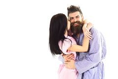Young satisfied couple in love cuddling gently in pajamas, copy space. Relationship and weekend goals. Couple in love. Hugging, girl kissing macho, isolated on royalty free stock image
