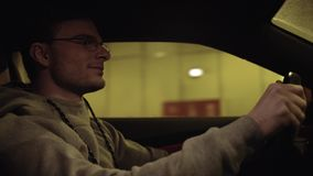 Young satisfied man driving car in underground tunnel. Young satisfied caucasian unshaved man in glasses and gray hoodie driving car in underground tunnel stock footage