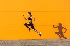 Young satisfied sporty beautiful woman with fit body jumping and running, hurry up against orange wall background. Gymnast jumping. High with toothy smile, full royalty free stock image