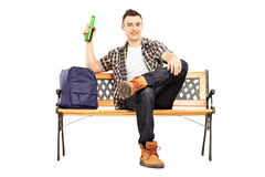 Young satisfied student sitting on a bench and drinking beer stock photos