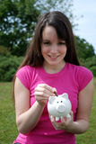 Young saver putting coin in piggy bank Royalty Free Stock Photo