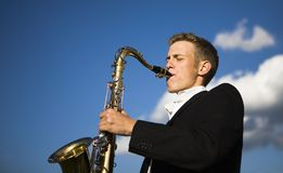Young saxophone player. Playing his instrument outdoors with blue sky and cloud background. Very narrow selective focus on the intense facial expression stock images