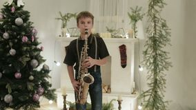 A handsome boy plays the saxophone in the background of the Christmas tree. Holiday home concert stock video footage