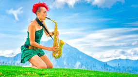 Young saxophonist (woman with the red hair) playing saxophone in Stock Images