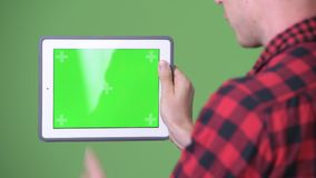 Young Scandinavian businessman using digital tablet against green background. Studio shot of young Scandinavian businessman using digital tablet against chroma stock video