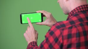 Young Scandinavian businessman using mobile phone against green background. Studio shot of young Scandinavian businessman using mobile phone against chroma key stock footage