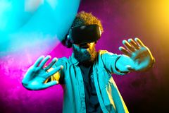 Young scared bearded hipster man with curly hair wearing virtual reality goggles in studio in neon lights. Smartphone. Using with VR headset royalty free stock photography