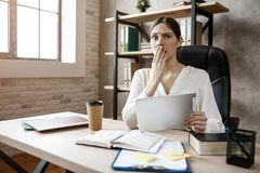 Young scared buisnesswoman in room at table. She hold tablet and cover mouth with hand. Model look straight forward. Young scared buisnesswoman in room at table royalty free stock photo