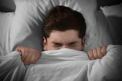 Young scared man lying in bed. At home Stock Photography